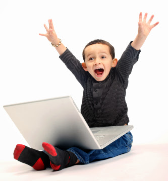 a young mixed race boy shouts with delight whilst using a laptop computer